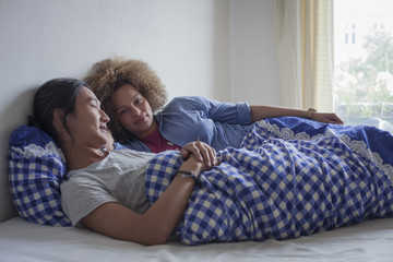 Young couple lying on bed against white wall by window at home