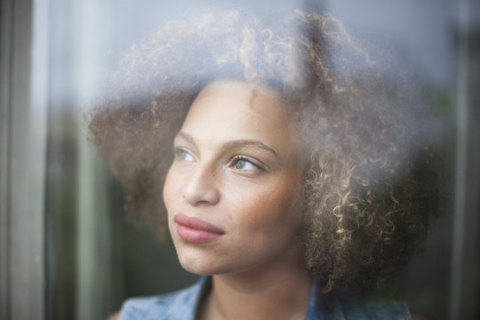 Close up of thoughtful woman looking through glass window