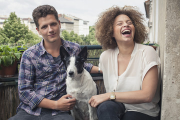 Happy young friends sitting with dog in balcony