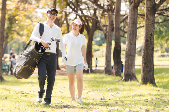 Asian couple playing golf. man teaching woman to play golf while standing on field