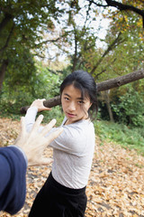 Aggressive woman holding stick in front of hand at park