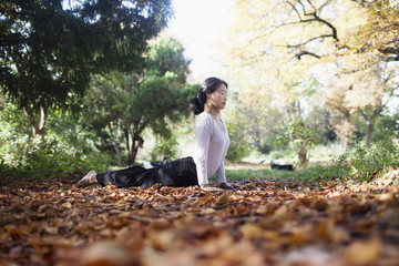 Woman performing yoga while lying on dry leaves by trees at park