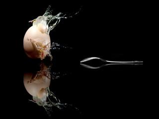 Ei - Egg mit Löffel / with spoon  explodiert / explodes Hintergrund Schwarz / background black