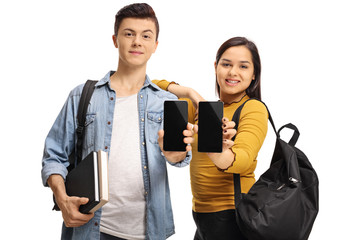 Teenage students with books and backpacks showing phones