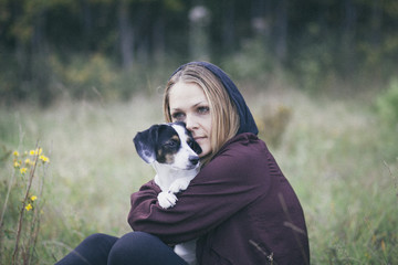 Thoughtful woman embracing dog while sitting on grassy field