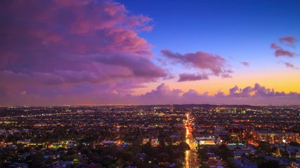 Fotobehang - Los Angeles cityscape changing from colorful sunset to night. 4K UHD Timelapse.