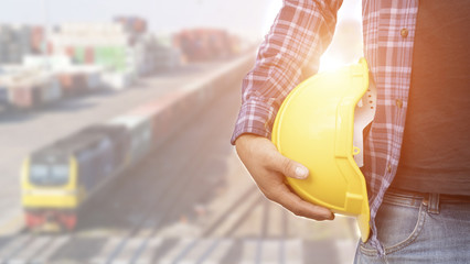 Engineer hold in hand yellow helmet in front of construction blur background.