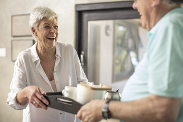 Happy senior woman serving coffee on a tray to husband