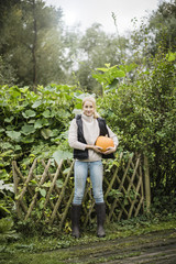 Portrait of smiling young woman holding pumpkin in garden