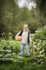 Portrait of smiling young woman with spade and pumpkin in garden