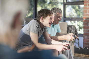 Grandfather and grandson playing video game on couch at home