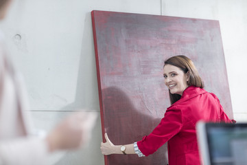 Businesswoman in office holding a red painting