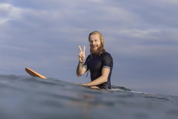 Portrait of happy man posing on surfboard in the sea