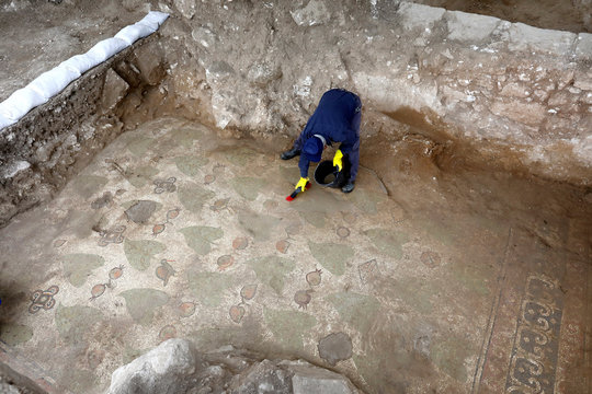 A worker cleans an ancient mosaic floor, decorated with birds, leaves and pomegranates, revealed during an Israeli Antiquities Authority excavation of a Christian pilgrimage center which is around 1,500 years old in Beit Shemesh