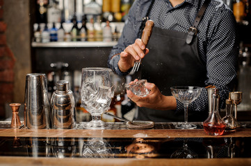 Barman crushing a big ice cube for making a cocktail