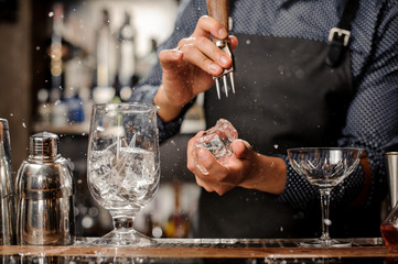 Bartender crushing a big piece of ice for a cocktail