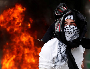 A Palestinian protester throws a stone at Israeli forces during a protest against U.S. President Donald Trump's decision to recognize Jerusalem as the capital of Israel, near Qalandia checkpoint near the West Bank city of Ramallah