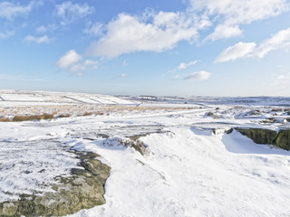 The snow covered Derbyshire Peak District sits under a blue winter sky.