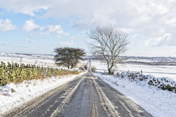 Down the long, straight and narrow road, between snow covered moorland.
