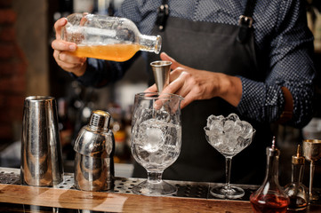 Barman pouring syrup into the large cocktail glass
