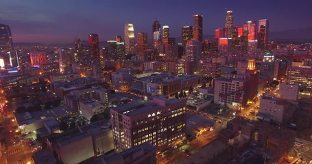 Fototapete - Aerial view illuminated city downtown Los Angeles skyline at dusk night. 4K UHD