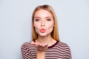 I love you my darling! Close up portrait of beautiful cute lovely charming happy woman clothed in striped outfit, she is sending an air kiss, isolated on grey background