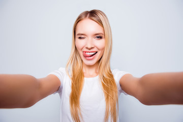 Joyful delightful happy excited attractive young blonde is giving a wink and taking a selfie, isolated on grey background
