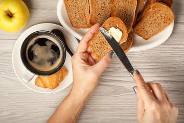View of female hands spreading butter on toast, cup of black coffee, croissant, bread and apple