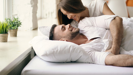 Young beautiful and loving couple wake up at the morning. Attractive woman kiss and hug his husband in bed