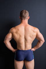 young athletic male with an athletic figure. part of body: back is broad, inflated muscle, elastic ass. clear skin and short hair. a beach boy shorts. guy posing on a black textured background
