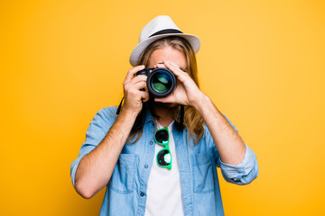 Portrait of guy in hat looking at photo camera, shooting photographs during excursion, making photosession over yellow background