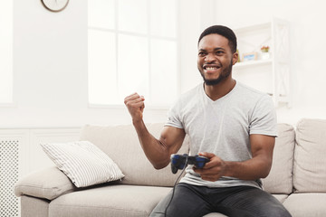 Happy young african-american man at home playing video games and wins
