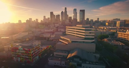 Fototapete - Aerial view city Los Angeles downtown skyline sunset Camera flying forward 4K