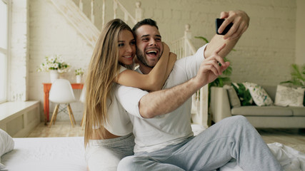 Young beautiful and loving couple take selfie picture on smartphone camera while sitting in bed at the morning
