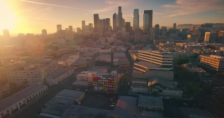 Fototapete - Aerial view city Los Angeles downtown skyline sunset Camera panning sideways 4K