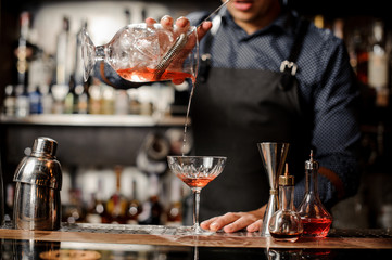 Barman pouring red alcoholic drink into the cocktail glass