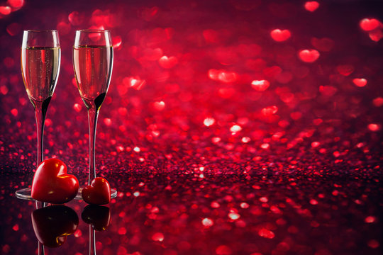 Two glasses of champagne with red heart shape bokeh on background.