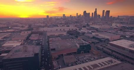 Fotobehang - Aerial industrial warehouses rooftops Los Angeles downtown skyline sunset 4K UHD