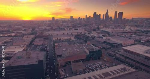 Fotobehang Aerial industrial warehouses rooftops Los Angeles downtown skyline sunset 4K UHD