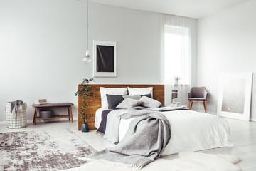 Dark poster in bright bedroom