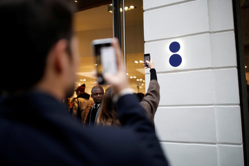 Shoppers take photos of the Colette Concept Store logo as the streetwear and high fashion shop closes its doors after 20 years of business in Paris