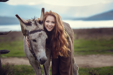 Tuinposter Ezel A girl with curly red hair in fashionable clothes in the style of Provence hugs a cute donkey