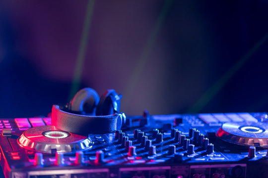 The DJ console cd mp4 deejay mixing desk Ibiza house music party in nightclub with colored disco lights.