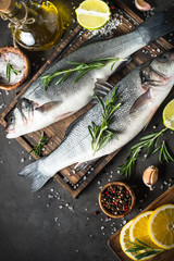 Fresh fish seabass on black stone table/ Top view.