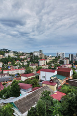 Panorama of the city of Sochi from a bird's eye view/Panorama of Sochi from the air. Houses, streets, trees, the sky are visible. In the distance you can see the sea. Sochi, Russia, cityscape