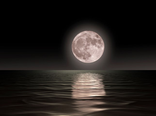Red moon rising on the ocean.