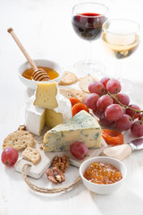 molded cheeses, fruit and snacks on a white wooden background, vertical