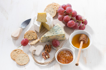 molded cheeses, fruit and snacks on a white wooden board, top view