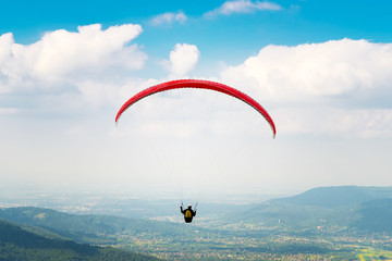 Paraglider flying over the fields on a sunny day. Poland.