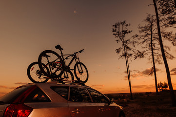 Bike transportation - two bikes on the roof of a car. Sunset.